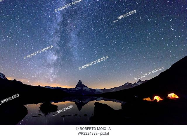 Camping under the stars and Milky Way with Matterhorn reflected in Lake Stellisee, Zermatt, Canton of Valais, Swiss Alps, Switzerland, Europe