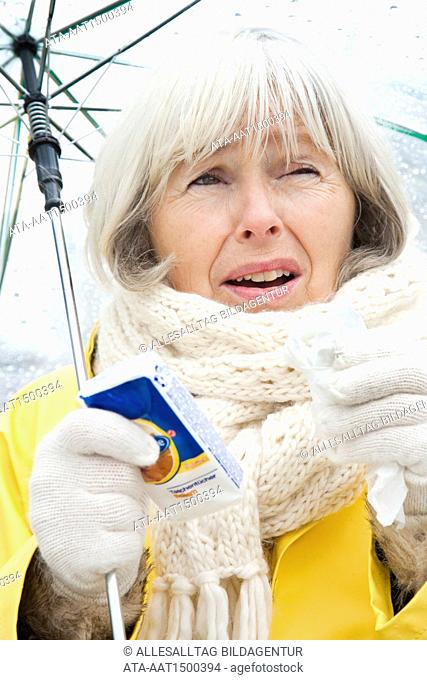 Elderly person has a cold with umbrella