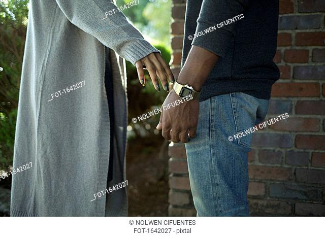 Midsection of woman touching man's hand against brick wall