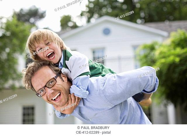 Man carrying son piggyback outdoors