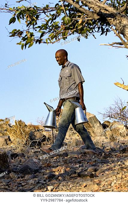 Staff person carrying water in tin cans at Huab Under Canvas, Damaraland, Namibia, Africa