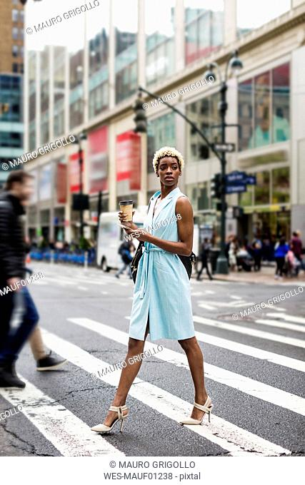 USA, New York, young blonde african-american woman with cup of coffee and smart phone crossing street