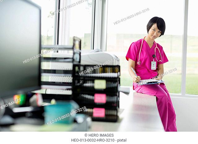 mid adult asian medical technician writing on chart