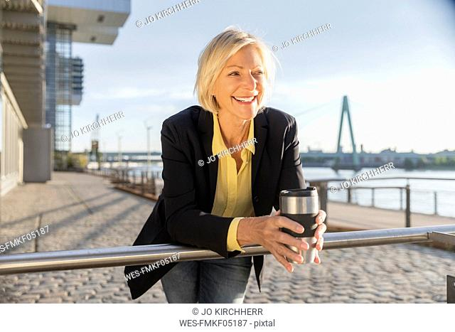 Happy senior businesswoman with takeaway coffee at the riverside