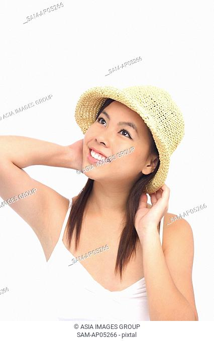 Young woman wearing hat, looking away, smiling