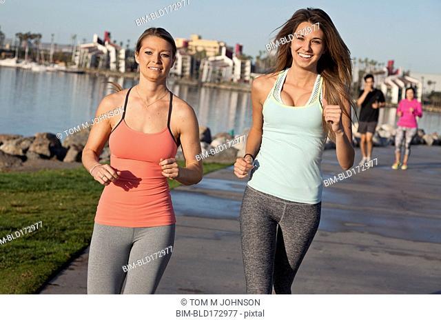 Caucasian women jogging at waterfront