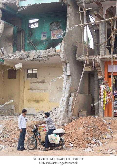 General store and motorbike, a building that was partly removed to make way for upcoming highway in Yelahanka, Karnataka, India