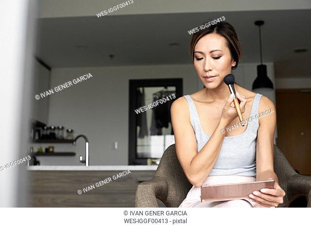 Woman at home using hand mirror applying makeup
