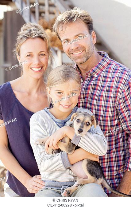 Portrait of smiling family holding puppy