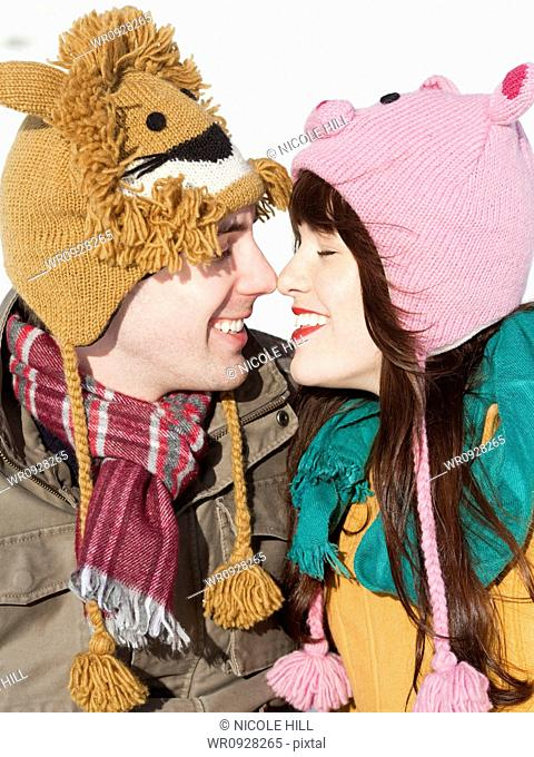 Orem, Utah, USA, boyfriend and girlfriend wearing funny knit hats touching with noses