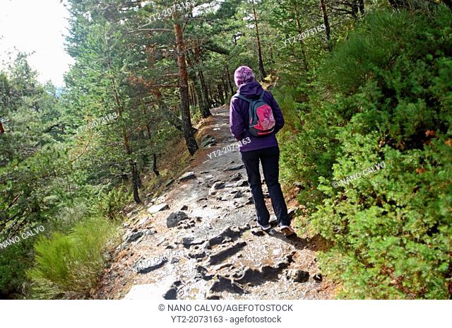 Young woman hiking in Peñalara, highest mountain peak in the mountain range of Guadarrama, Spain