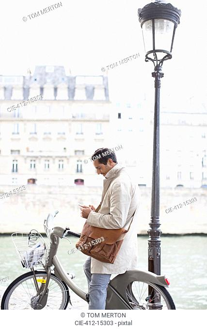 Businessman using cell phone on bicycle along Seine River, Paris, France