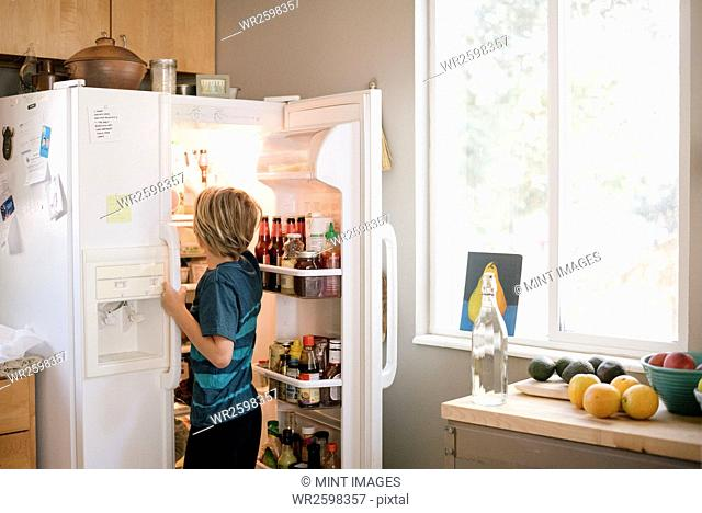 Family preparing breakfast in a kitchen, boy standing at an open fridge