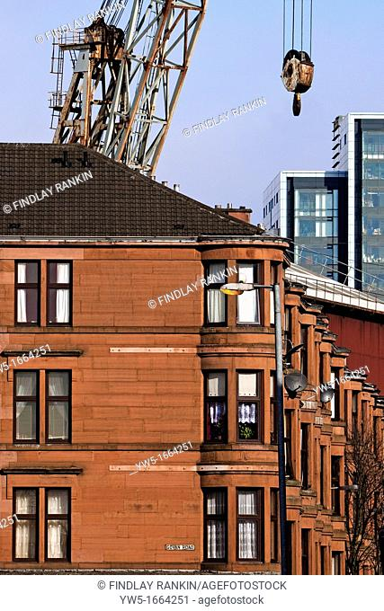 Glasgow sandstone tenement building with a luffing crane from the shipyard and a new office building in the distance  Govan Road, Glasgow, Scotland
