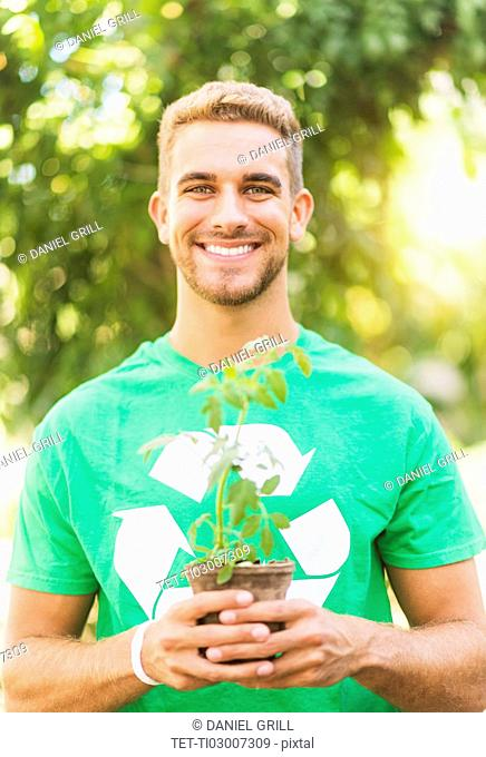 Portrait of young man holding potted plant