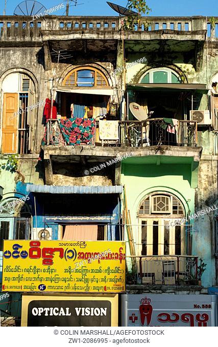 Old building terraces with signs in Myanmarese script in Yangon in Myanmar