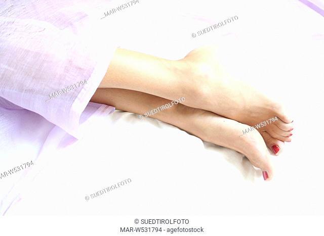 piedi di donna sul letto