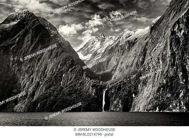 Waterfall from mountains over remote river, Milford Sound, Fiordland, New Zealand