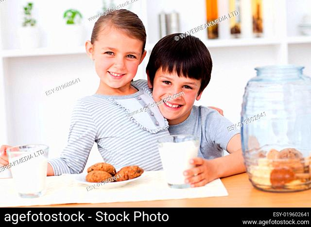 Portrait of smiling brother and sister eating biscuits