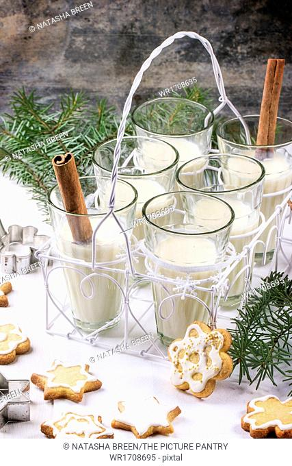 Christmas cookies assorted and glasses of milk cocktail, served with christmas tree branch on wooden table