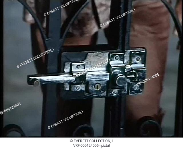 Hands opening gate lock