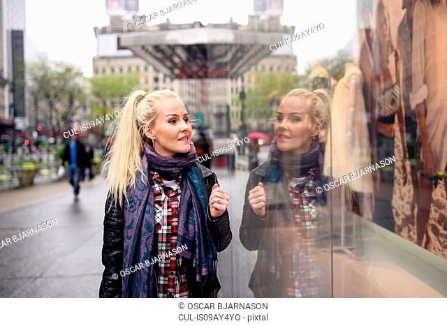 Female tourist window shopping, New York, USA