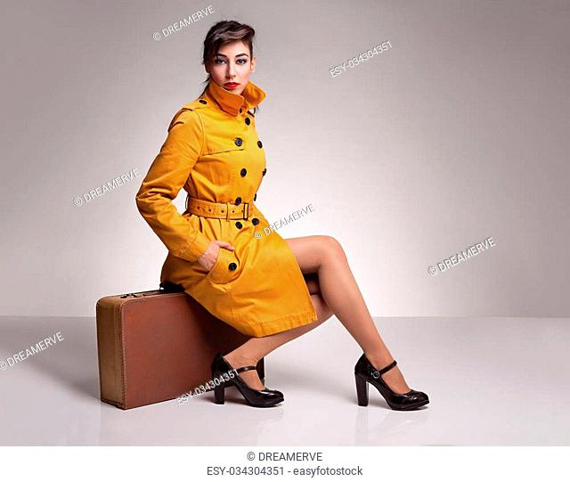 beautiful brunette model with her hand in her pocket posing with her yellow overcoat while sitting on her retro suitcase on grey background