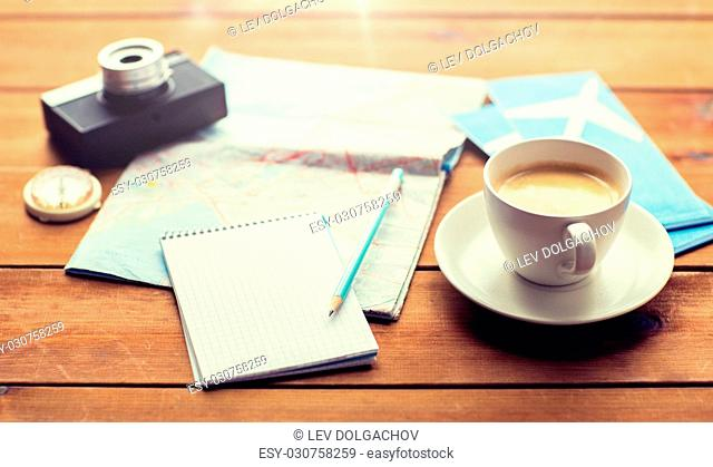vacation, tourism, travel and objects concept - close up of blank notepad with map, coffee and airplane tickets
