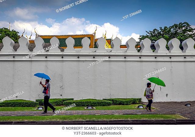 Asia. Thailand, Bangkok. People with umbrella walking front of king's palace wall