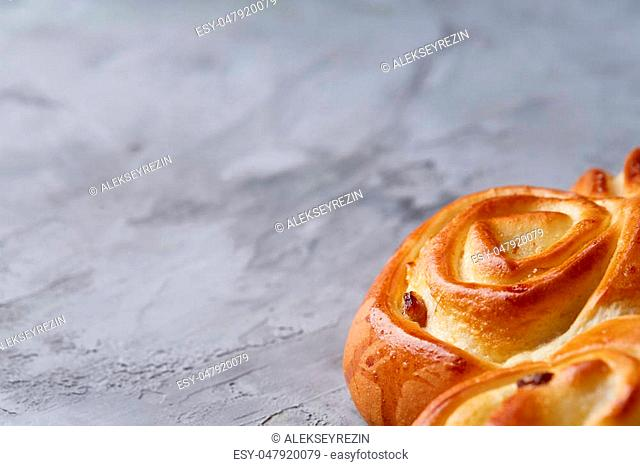 Homemade rose bread with raisins over white textured background, close-up, top view, shallow depth of field. Aromatic delicious pastry