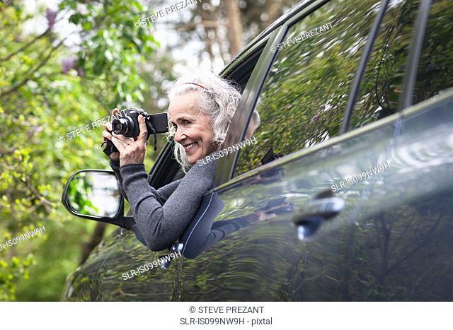 Senior woman photographing man car