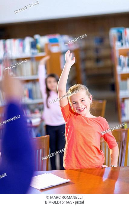Student raising her hand in library