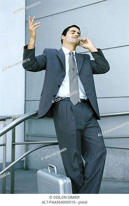 Businessman leaning against railing and using cell phone, making frustrated gesture with hand
