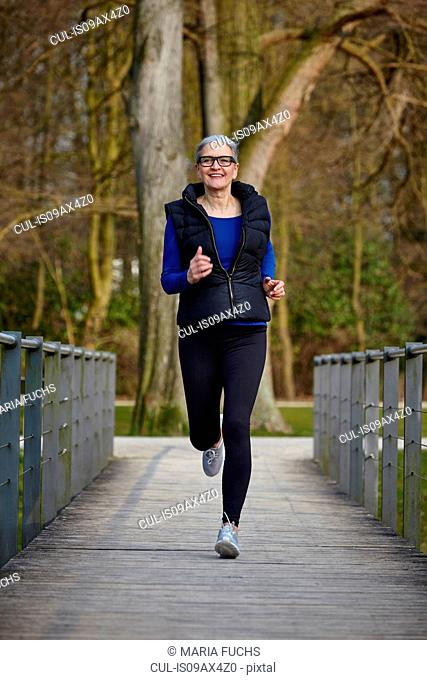 Full length front view of woman on wooden path jogging, looking at camera smiling