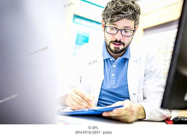 Optometrist writing prescription in optometrist's shop