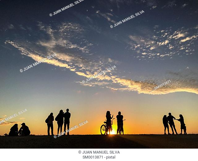 People looking at sunset on levee of Everglades National Park, Florida, USA