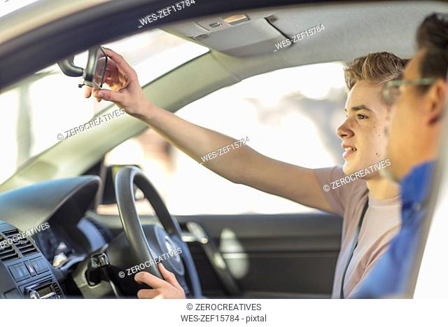 Learner driver with instructor in caradjusting rear view mirror