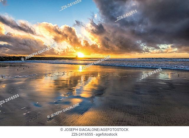 Clouds reflecting off wet sand. Sunset at South Mission Beach. San Diego, California, United States