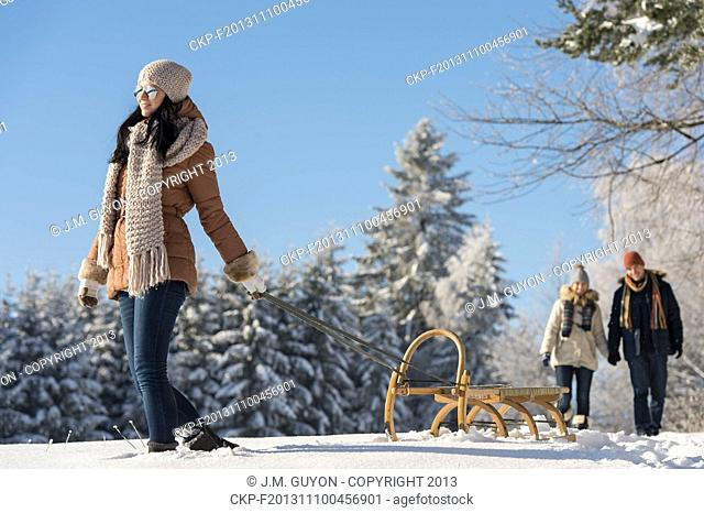 Sunny winter day woman pulling sledge couple walking in snow