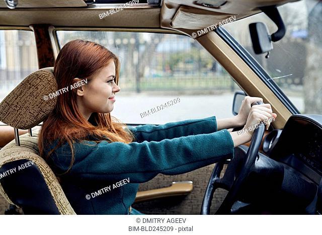 Smiling Caucasian woman driving car