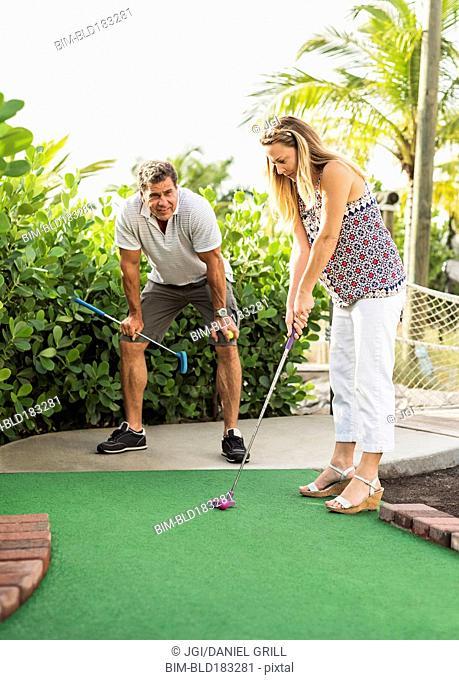 Caucasian couple playing miniature golf