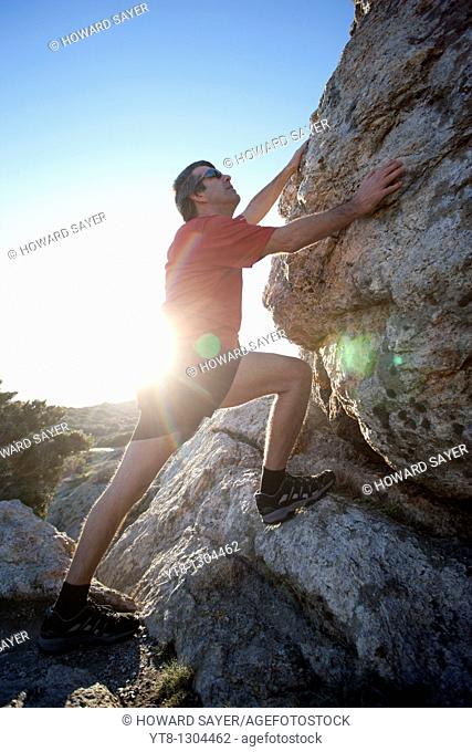 Man climbing up over rocks