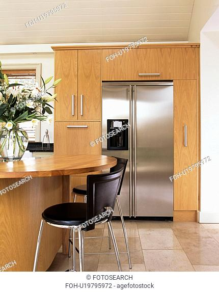 Black chairs with chrome legs at breakfast bar in modern kitchen with large stainless steel American-style refrigerator
