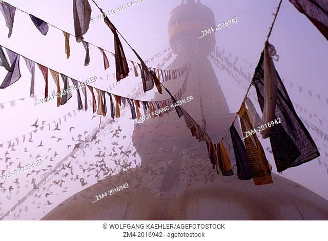 NEPAL, KATHMANDU, BOUDHNATH, TIBETAN STUPA (TEMPLE) IN FOG, PRAYER FLAGS, PIGEONS