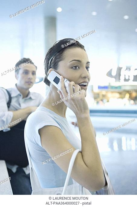 Woman using cell phone in airport