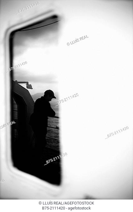A man leaning on the railing of a boat at looking at the sea, reflected in a window. Croosing the Mediterranean Sea from Ciutadella, Menorca to Alcudia