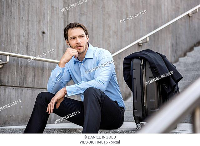 Businessman with rolling suitcase sitting on stairs