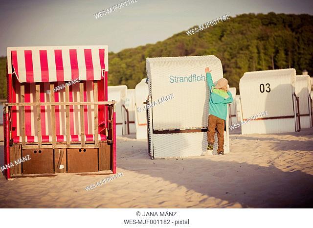 Germany, Mecklenburg-Western Pomerania, Ruegen, Boy on beach with beach chairs