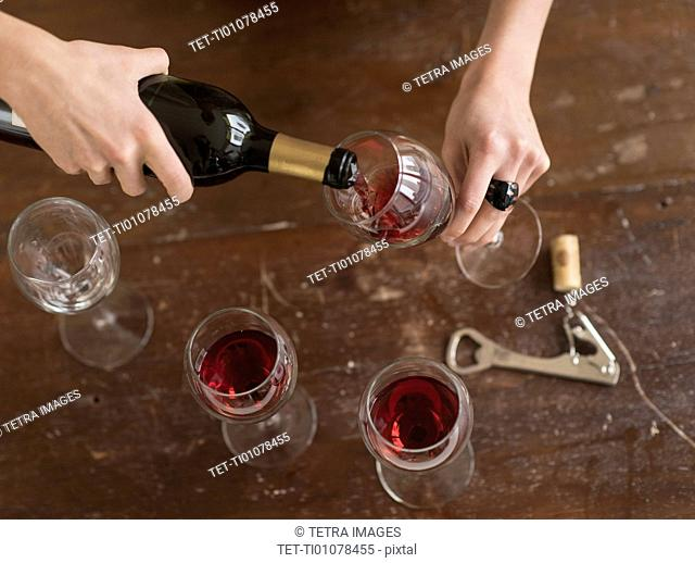 Elevated view of woman pouring red wine