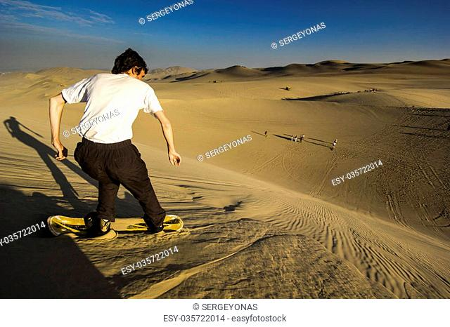 riding man on sandboard at desert at sunset with sunbeam against sun